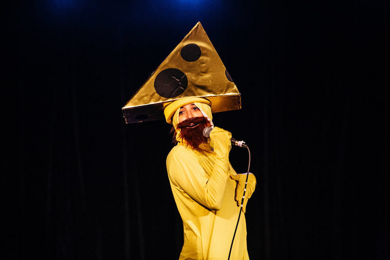 "Mr. Cheesehead (Debbie Zukerman) singing ""Another one bites the Cheese"" in You'll Never Guess Where I Hid the Cheese, Sydney Fringe 2017"